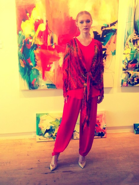 "Essdea wears Carter Smith's designs while standing in front of Vicky Barranguet's ""Somewhere Between my Heart and Ear"" (large painting in the center), ""Greenscapes"" (bottom left) and ""Undefined Elements"" (bottom right)."
